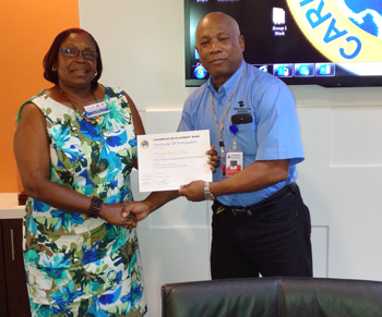 Mission Accomplished – Retired Brigadier General Earl Arthurs, Operations Specialist at CDEMA presents Certificate to Mrs. Brenda Thomas-Odlum, Director of the Community Development Division of the Government of Antigua and Barbuda.