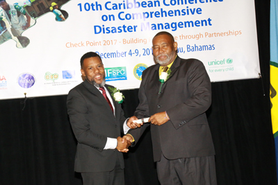 Mr Ronald Jackson, Executive Director of CDEMA (left) presenting the CDEMA Lifetime Achievement Award to Mr. Philmore Mullin, Director of the National Office of Disaster Services, Antigua and Barbuda.