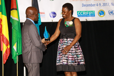 Left - Mr Jeremy Collymore presenting the Jeremy Collymore Award for Research in Humanitarian Response and Disaster Risk Management to Dr. Denise Thompson, the first recipient of the Award.