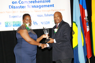 The Hon. Samantha Marshall, Minister of Social Transformation and Human Resource Development, Antigua and Barbuda and Chair of the CDEMA Council of Ministers (left) presenting the CDEMA Council Award to General Earl Arthurs.