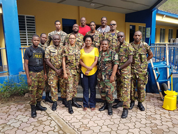 CARICOM Disaster Relief Unit (CDRU) with Superintendent St. Clair Amory (red top), Constable Ricardo Jones from the Royal Virgin Islands Police Force (grey top) and Ms. Donna Pierre of the CDEMA Coordinating Unit standing in front of the rehabilitated Alexandrina Maduro Primary School