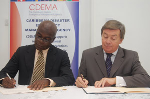 Mr. Jeremy Collymore, Executive Director, CDEMA and Ambassador Acquarone sign the agreement