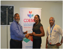 Mr. Philmore Mullin, Director of NODS, Antigua & Barbuda and Brigadier General (Rtd) Earl Arthurs, Consultant with the CDEMA CU captured above presenting a Grocery Voucher to Salome Deazle
